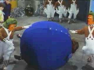 The fully inflated blueberry girl, Violet Beauregarde, is being rolled around on the floor of the Inventing Room by the Oompa Loompas in the movie, 'Willy Wonka and the Chocolate Factory' (1971). Her head, hands, and feet are sticking out of her spherical blue body.