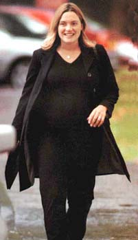 A view of very pregnant Kate Winslet walking outside and smiling. She is wearing a black pantsuit.