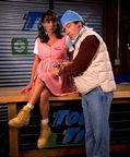 Debbe Dunning is sitting wearing her costume on the Home Improvement 'Tool Time' set. Tim Allen is dressed like a doctor and is holding a stethoscope to her belly.