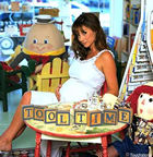 Debbe Dunning is sitting at a small table in the children's shop with 'Tool Time' spelled out in front of her using alphabet blocks. She is holding the front curve of her belly with her right hand.
