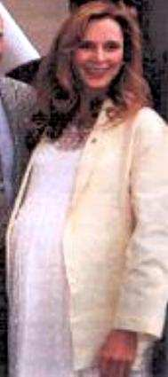 A cropped photo of Gates McFadden (Dr. Crusher on Star Trek: The Next Generation) from a group shot of her standing with Gene Roddenberry and the casts of Star Trek and Star Trek: The Next Generation at the dedication of the Gene Roddenberry building on the Paramount Pictures lot in 1989. She is wearing a long white dress and light yellow jacket. She is smiling, and her wonderfully huge eight month pregnant belly looks terrific.